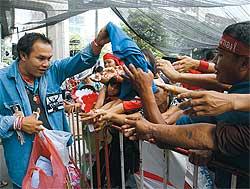 Responsables de los Camisas Rojas reparten camisas de otros colores a sus simpatizantes. Foto: The bangkok Post