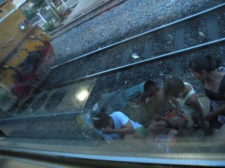 Estas dos madres estan sentadas conversando mientras sus hijos pululan tranquilamente por las vias del tren